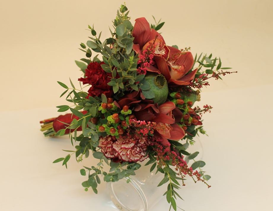 An informal bridal bouquet in red tones