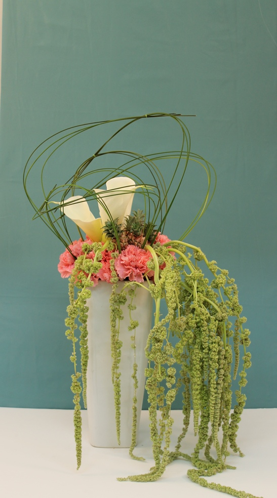 Tall vase arrangement with roses, hanging amaranthus and pineapple