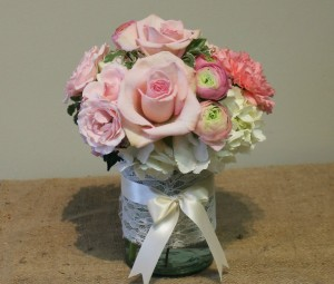 Pink roses and ranunculus with white hydrangea in a lace-wrapped vase