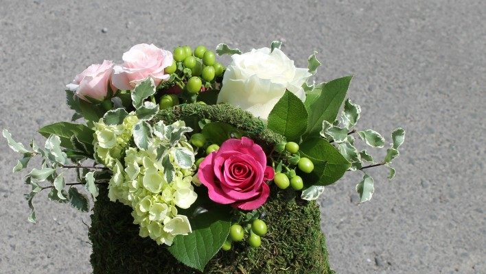 Pink, white and green arrangement in a purse