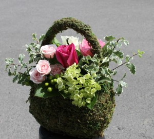 Feminine floral design in a purse made of moss