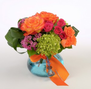 Orange, hot pink and green flowers in blue vase